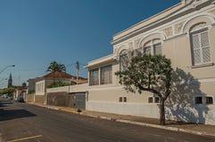 Gammalt utsmyckat radhus i en tom gata med träd på trottoaren i en solig dag på San Manuel royaltyfri bild