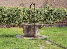 gammalt väl mot efterkrav att bevattna i den Pomposa abbotskloster i Italien Royaltyfri Bild
