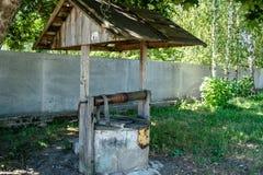 Gammalt vatten väl under lokaliserat i byn under solig dag royaltyfri bild
