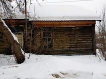 Gammalt ?vergett hus med ett brutet f?nster p? bakgrunden av den insn?ade vintern arkivfoto