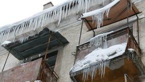 Gammalt ?vergett hus och dess balkong med ett enormt belopp av sm?ltande istappar i vinter arkivfilmer