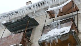 Gammalt ?vergett hus och dess balkong med ett enormt belopp av sm?ltande istappar i vinter stock video
