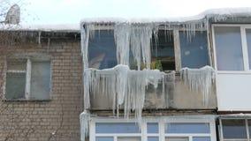 Gammalt ?vergett hus och dess balkong med ett enormt belopp av sm?ltande istappar i vinter lager videofilmer