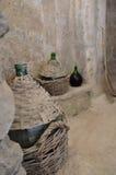 Gammalt vin draided flaskor i en källare Arkivfoto