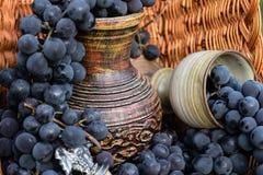 Gammalt vinkanna och leraexponeringsglas, winemakingemblem och en kork Arkivbild