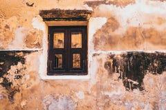 Gammalt vitt träfönster för tappningsignal på den lantliga gula betongväggfasadbakgrunden arkivfoto