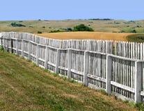Gammalt vitt wood staket i ett fält Arkivbild