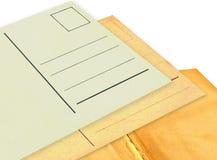Gammalt vykort och fluga-blad på vit Arkivfoto