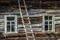Gammalt wooren huset med två fönster och stege arkivfoton