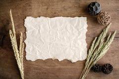 Gammalt wrinkldpapper på gammal wood bakgrund med den torkade blomman Royaltyfria Bilder