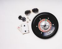 Gampling tools. Still life of a gambler. Background of a casino table with roulette wheel, sunglasses, Poker chips, dices, a model car and a skull. Ready to stock images