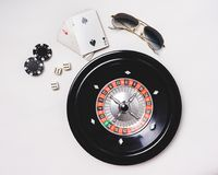 Gampling tools. Still life of a gambler. Background of a casino table with roulette wheel, sunglasses, Poker chips and dices. Ready to play. Las Vegas concept stock photo