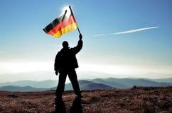 Ganador acertado del hombre de la silueta que agita la bandera alemana encima de la montaña imagen de archivo libre de regalías