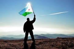 Ganador acertado del hombre de la silueta que agita la bandera de Djibouti encima de la montaña fotos de archivo
