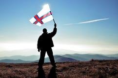 Ganador acertado del hombre de la silueta que agita la bandera de Faroe Island encima de la montaña foto de archivo libre de regalías