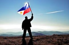 Ganador acertado del hombre de la silueta que agita la bandera de Filipinas encima de la montaña fotos de archivo