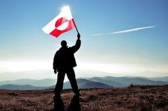 Ganador acertado del hombre de la silueta que agita la bandera de Groenlandia encima de la montaña imágenes de archivo libres de regalías