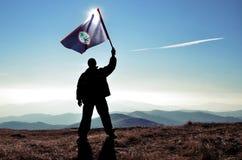 Ganador acertado del hombre de la silueta que agita la bandera de Guam encima de la montaña imágenes de archivo libres de regalías