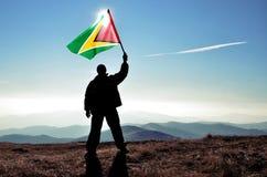 Ganador acertado del hombre de la silueta que agita la bandera de Guyana encima de la montaña imagenes de archivo