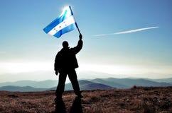 Ganador acertado del hombre de la silueta que agita la bandera de Honduras encima de la montaña fotos de archivo