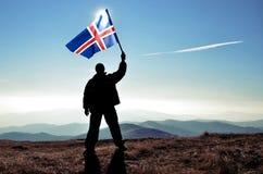 Ganador acertado del hombre de la silueta que agita la bandera de Islandia encima de la montaña fotos de archivo libres de regalías