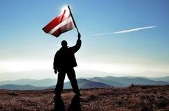Ganador acertado del hombre de la silueta que agita la bandera de Letonia encima de la montaña foto de archivo libre de regalías