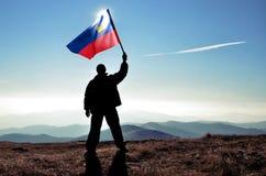 Ganador acertado del hombre de la silueta que agita la bandera de Liechtenstein encima de la montaña fotografía de archivo libre de regalías