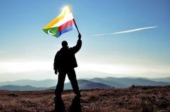Ganador acertado del hombre de la silueta que agita la bandera de los Comoro encima de la montaña fotografía de archivo libre de regalías