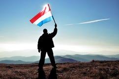 Ganador acertado del hombre de la silueta que agita la bandera de Luxemburgo encima de la montaña fotos de archivo libres de regalías