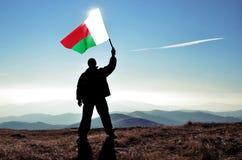 Ganador acertado del hombre de la silueta que agita la bandera de Madagascar encima de la montaña fotos de archivo