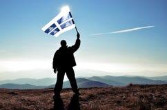 Ganador acertado del hombre de la silueta que agita la bandera de Martinica encima de la montaña imagen de archivo