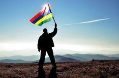 Ganador acertado del hombre de la silueta que agita la bandera de Mauricio encima de la montaña imagen de archivo