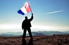 Ganador acertado del hombre de la silueta que agita la bandera de Mayotte encima de la montaña foto de archivo