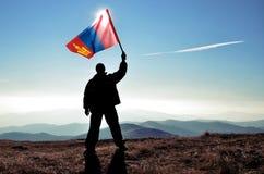 Ganador acertado del hombre de la silueta que agita la bandera de Mongolia encima de la montaña imagenes de archivo