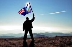 Ganador acertado del hombre de la silueta que agita la bandera de Montserrat encima de la montaña foto de archivo
