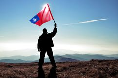 Ganador acertado del hombre de la silueta que agita la bandera de Myanmar encima de la montaña foto de archivo