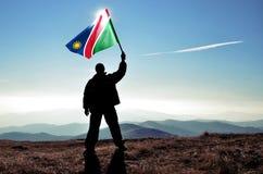 Ganador acertado del hombre de la silueta que agita la bandera de Namibia encima de la montaña fotos de archivo libres de regalías