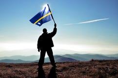Ganador acertado del hombre de la silueta que agita la bandera de Nauru encima de la montaña imagenes de archivo