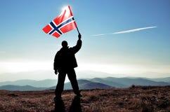 Ganador acertado del hombre de la silueta que agita la bandera de Noruega encima de la montaña imágenes de archivo libres de regalías