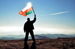 Ganador acertado del hombre de la silueta que agita la bandera de Omán encima de la montaña imágenes de archivo libres de regalías