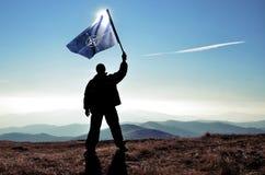 Ganador acertado del hombre de la silueta que agita la bandera de la OTAN encima de la montaña imágenes de archivo libres de regalías