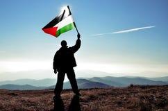 Ganador acertado del hombre de la silueta que agita la bandera de Palestina encima del mountai imagen de archivo libre de regalías