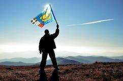 Ganador acertado del hombre de la silueta que agita la bandera de Pierre y de Miquelon encima de la montaña fotos de archivo libres de regalías