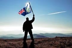 Ganador acertado del hombre de la silueta que agita la bandera de Pitcairn encima de la montaña foto de archivo libre de regalías