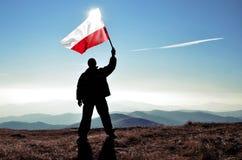 Ganador acertado del hombre de la silueta que agita la bandera de Polonia encima de la montaña imagen de archivo libre de regalías