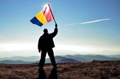 Ganador acertado del hombre de la silueta que agita la bandera de Rumania encima de la montaña fotografía de archivo