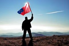 Ganador acertado del hombre de la silueta que agita la bandera de Samoa encima de la montaña fotos de archivo libres de regalías