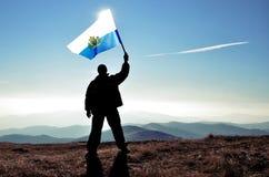 Ganador acertado del hombre de la silueta que agita la bandera de San Marino encima de la montaña foto de archivo
