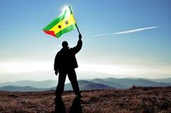 Ganador acertado del hombre de la silueta que agita la bandera de Sao Tome and Principe encima de la montaña fotos de archivo libres de regalías