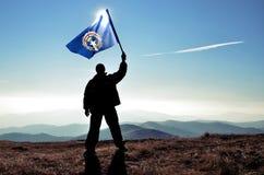 Ganador acertado del hombre de la silueta que agita la bandera septentrional de Mariana Islands encima de la montaña fotografía de archivo libre de regalías